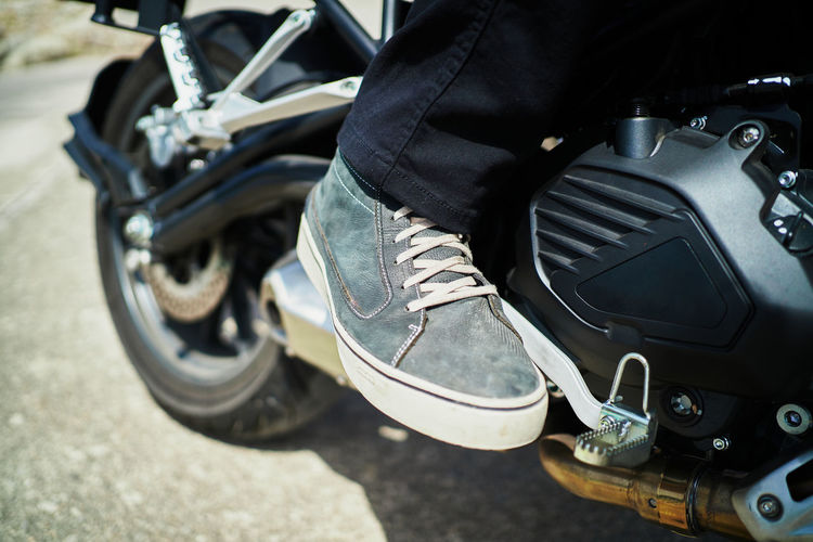 Low section of man with motorcycle on street