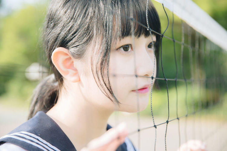 Close-up of thoughtful young woman looking away by net outdoors