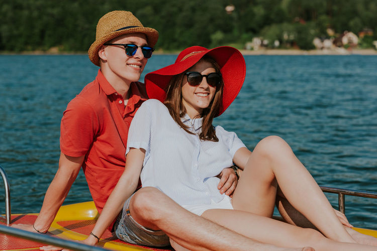 Portrait of smiling couple in love enjoying boating on the lake. Happy girlfriend and boyfriend relaxing on pedal boat on summer day. Boating Couple Holiday Hot Day Love Summertime Vacations Young Boat Boyfriend Caucasian Feet Girlfriend Lake Outdoors Pedalo Relax Resting River Sea Summer Sunglasses Sunhat Two People Water