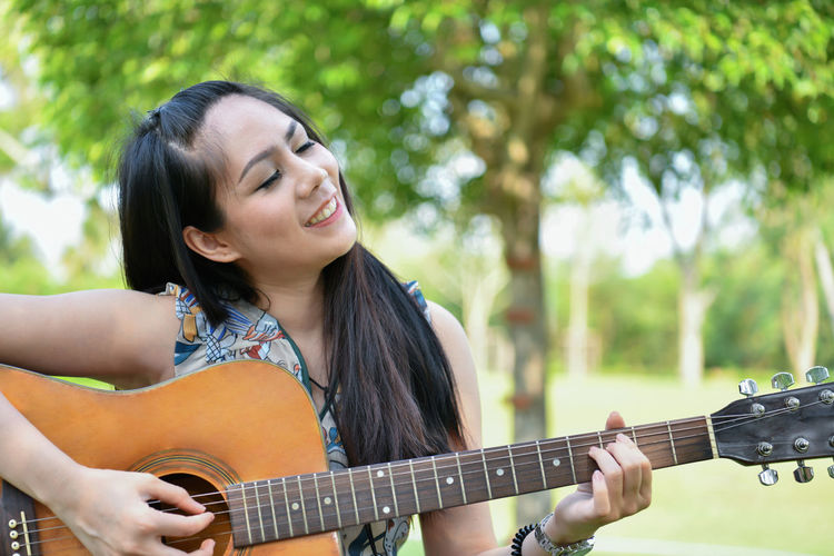 Smiling young woman playing guitar against trees at park