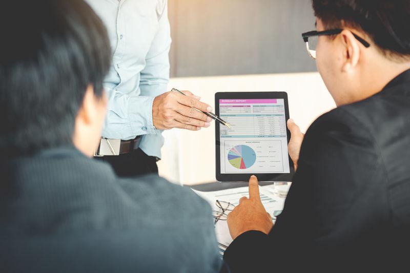 Businessmen Discussing Over Digital Tablet In Office