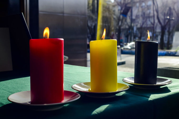 Lit candles symbolizing belgium flag on table at embassy building