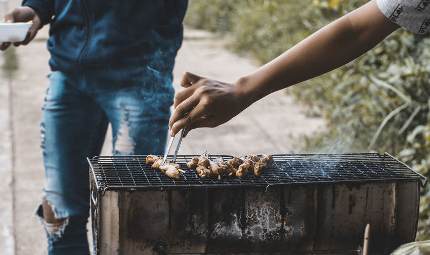 Cropped Hand Making Food On Barbecue Grill