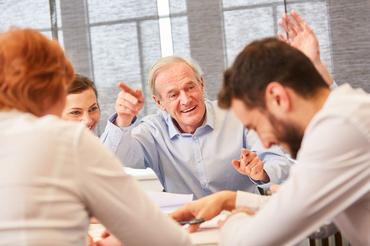 Cheerful business people having discussion in office