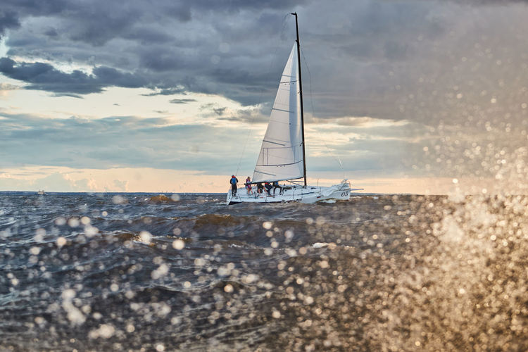Sailboat on sea shore against sky during sunset