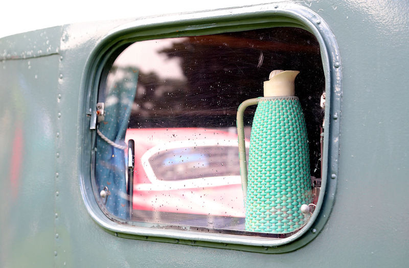 vintage thermos in a window of a mobile home Blue Close-up Coffee Curtain Day On The Way Land Vehicle Mobile Mobilehome Mode Of Transport No People Part Of Reflection Smllgrl Stationary Thermos Transportation Transportation Transportation Building - Type Of Building Vehicle Interior Vintage Vintage Cars Vintage Style Window Window View
