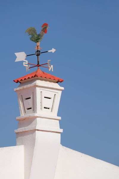 Low Angle View Clear Sky Built Structure Architecture Building Exterior Animal Themes Day No People Outdoors Sky Nature Compass Rooster North South East West Chimney Chimneys Traditional Design Decoration in Ilha Do Farol , Algarve Portugal MISSIONS: The Architect - 2017 EyeEm Awards