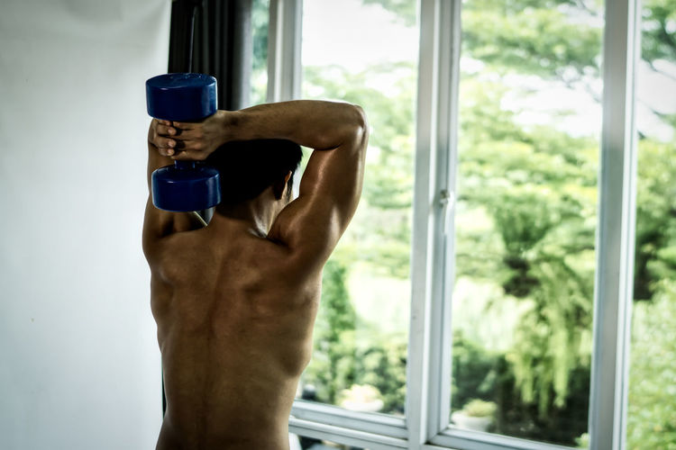 Shirtless Man Exercising While Standing By Window