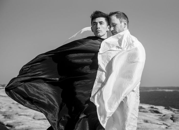 Young gay couple covered in textile standing on beach against sky