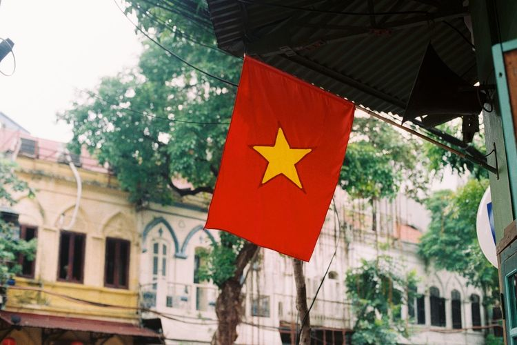 Low angle view of vietnamese flag hanging on building