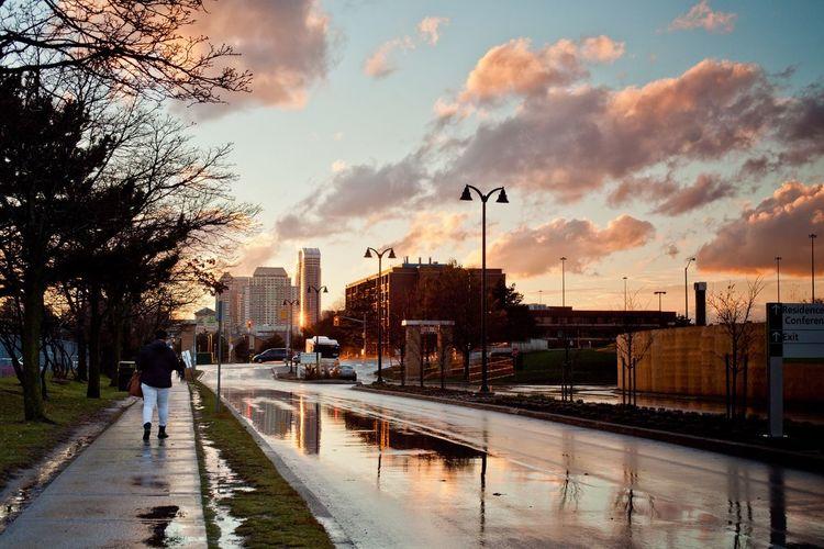 Rear View Of Man Walking On Wet Sidewalk By City Street Against Cloudy Sky