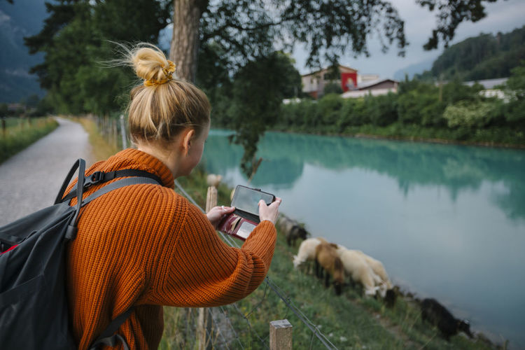 Woman photographing with mobile phone in lake