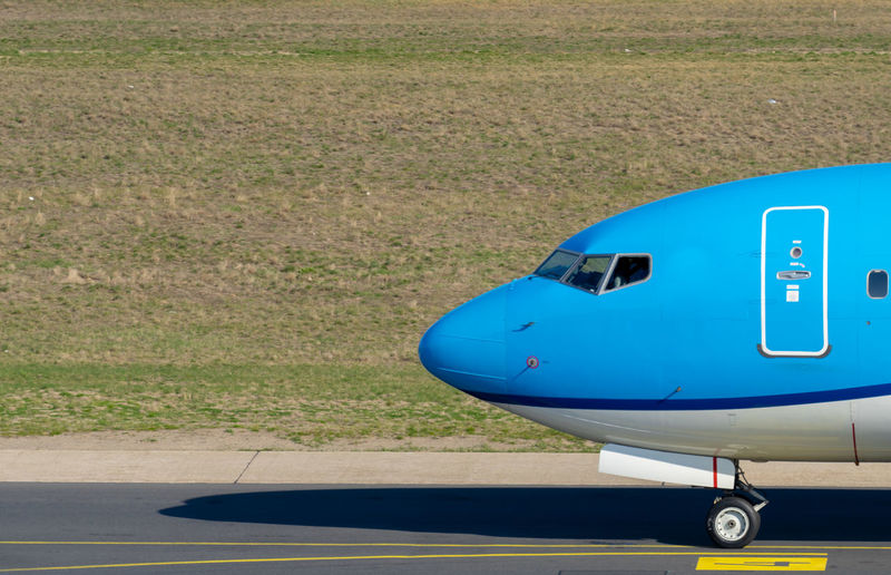 Wheel Absence Field Airport Runway High Angle View Sunlight Land Vehicle Road Outdoors Land Grass Air Vehicle Nature No People Day Mode Of Transportation Transportation Blue Airplane Plane Aeroplane Business Finance And Industry Business Traveling Travel Airport Public Transportation