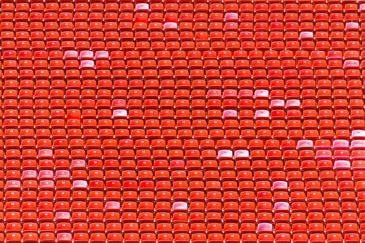 Full frame shot of empty red stadium seats