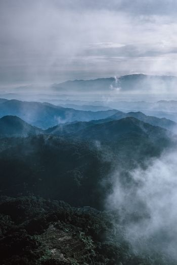 Scenic view of mountains against cloudy sky