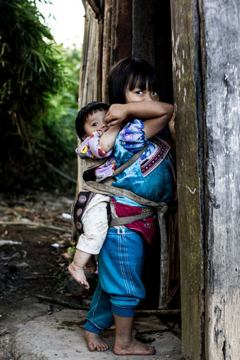 Cute Girl Carrying Sister On Back At Home