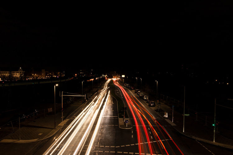 High angle view of light trails on road against clear sky at night