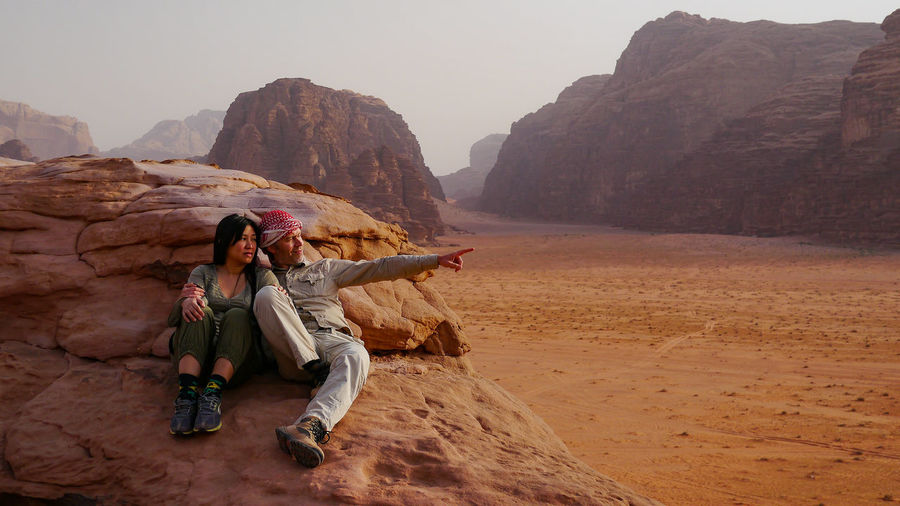 Couple Resting On Rock Formation At Wadi Rum