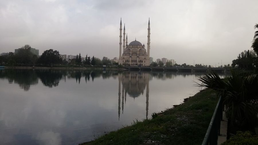 Mosque by reflection lake against sky