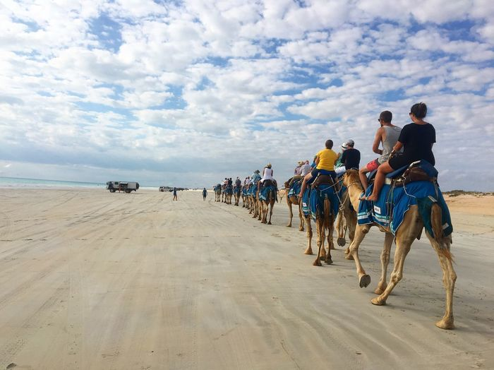 People riding on camels at beach against cloudy sky