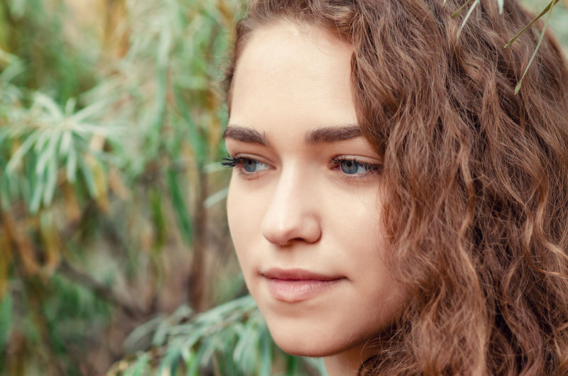 Portrait of girl with brown curly hair on background of green bush sea buckthorn, close-up face