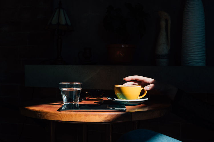 Female hand holding yellow cup of coffee Drink Food And Drink Yellow Cup Tablet Technology Freelance Coffee - Drink Coffee Mug Refreshment Table Cup Food Freshness Coffee Cup Drinking Glass Breakfast Glass Hot Drink Indoors  Copy Space Yellow Color Natural Light A New Perspective On Life Capture Tomorrow