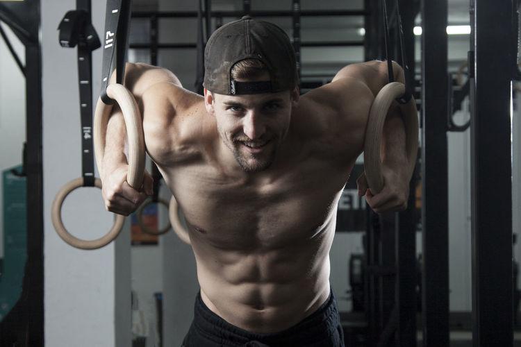Portrait of shirtless man exercising at gym