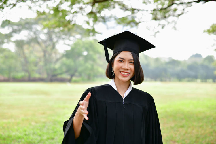 Achievement Ceremony Education Emotion Focus On Foreground Graduation Graduation Gown Happiness Mortarboard Outdoors People Portrait Smiling Standing Student Success University University Student Women Young Adult Young Women