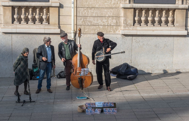 Street Musicians playing in the heart of Paris as a woman looks on Woman Adult Adults Only Banjo Player Buskers Day Guitar Men Music Musical Instrument Musician Outdoors People Performance Playing Upright Bass Player