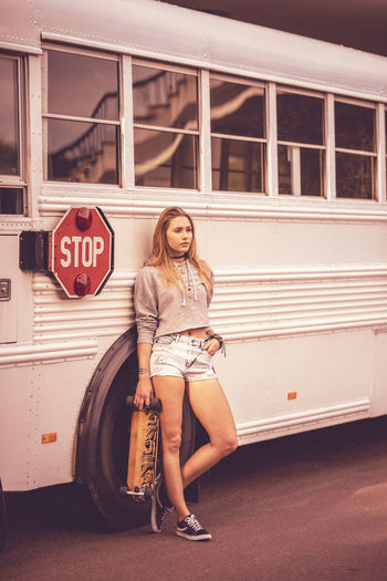Full length of young woman leaning on bus