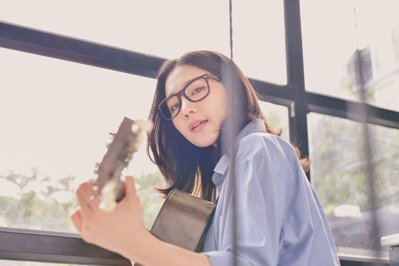 Adult Beautiful Woman Eyeglasses  Front View Hair Hairstyle Headshot Holding Indoors  Leisure Activity Lifestyles Long Hair One Person Portrait Real People Window Women Young Adult Young Women