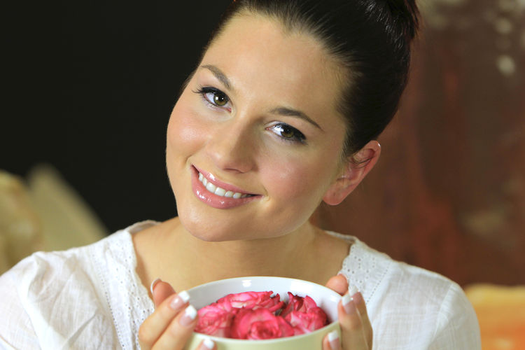 Close-Up Portrait Of Young Woman With Pink Roses In Bowl At Spa