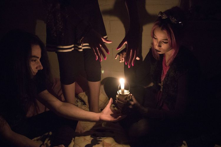 Friends With Illuminated Candle Practicing Witchcraft In Dark
