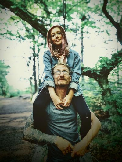 Smiling Father Carrying Daughter On Shoulders In Forest