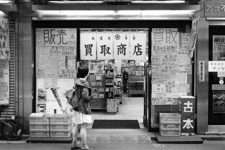 Reading Text Communication Real People Architecture City One Person Food And Drink Full Length Standing Business Non-western Script Casual Clothing Day Retail  Script Store Concession Stand Japan Japan Photography Travel Destinations Travel Tokyo Akihabara Shop Shopping Woman Monochrome Blackandwhite Black & White Streetphotography Street Street Photography Canon Japanese  Lettering Signage Urban City City Life The Traveler - 2019 EyeEm Awards The Street Photographer - 2019 EyeEm Awards