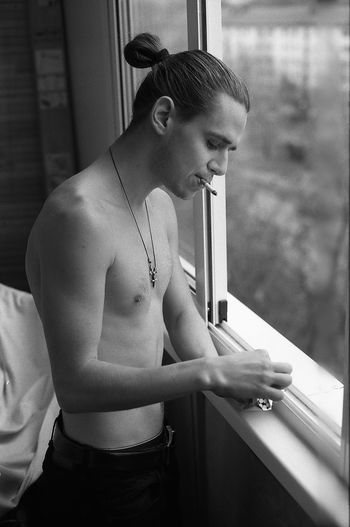 Shirtless young man smoking cigarette by window at home