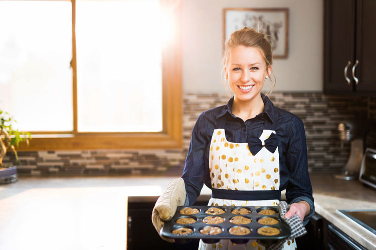 Cooking Adult Apron Baking Cheerful Chef Domestic Kitchen Domestic Life Domestic Room Food And Drink Front View Happiness Indoors  Kitchen Looking At Camera Muffins One Young Woman Only People Portrait Preparation  Service Smiling Sunflare Tray Young Adult