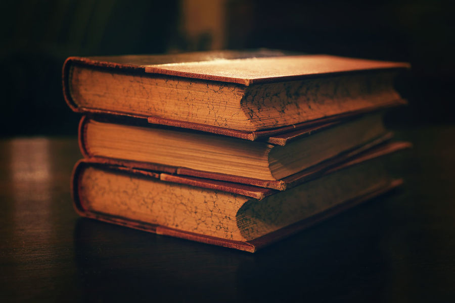 Close up stack of old vintage antique hardcover books on table in the dark Antique Dark Library Low Angle View Past Retro Aged Book Book Cover Close-up Education Focus On Foreground Group Of Objects Hardcover Hardcover Book History Indoors  Literature No People Old Stack Table Three Vintage Wisdom