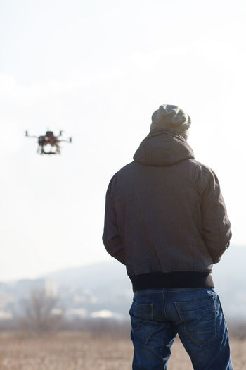 Rear View Of Mid Adult Man Flying Drone Against Clear Sky