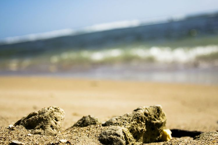 Close-up of rocks on beach against sky