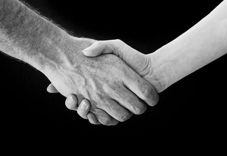 Cropped image of people doing handshake against black background