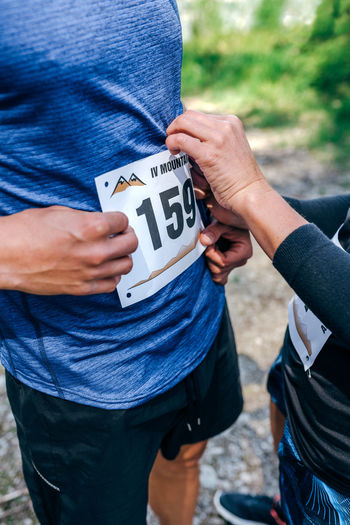 Midsection of man attaching marathon bib while standing in forest