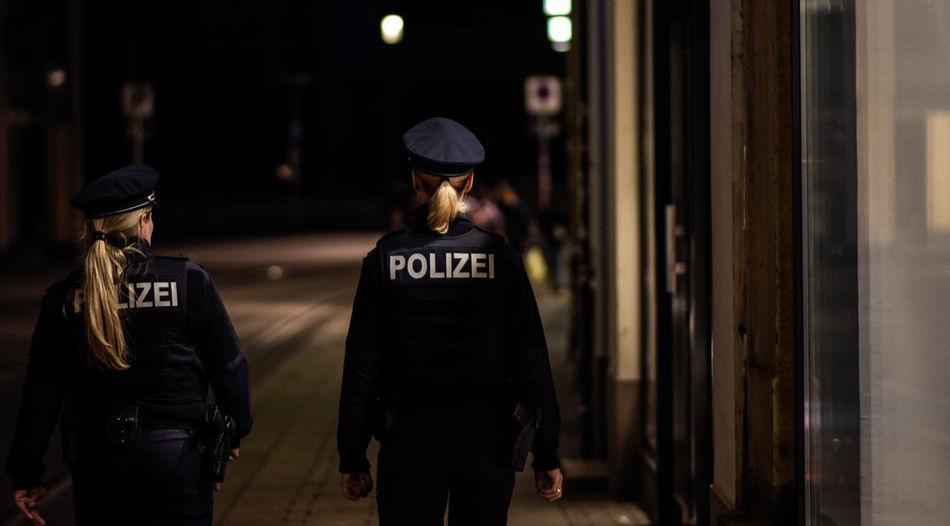 Rear view of policewomen walking on sidewalk in city at night