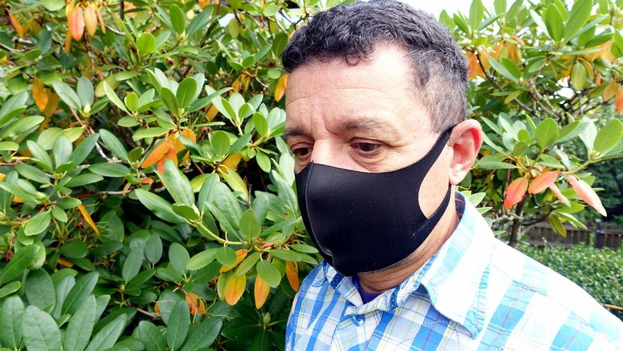 Close-up of man wearing mask standing by plant outdoors