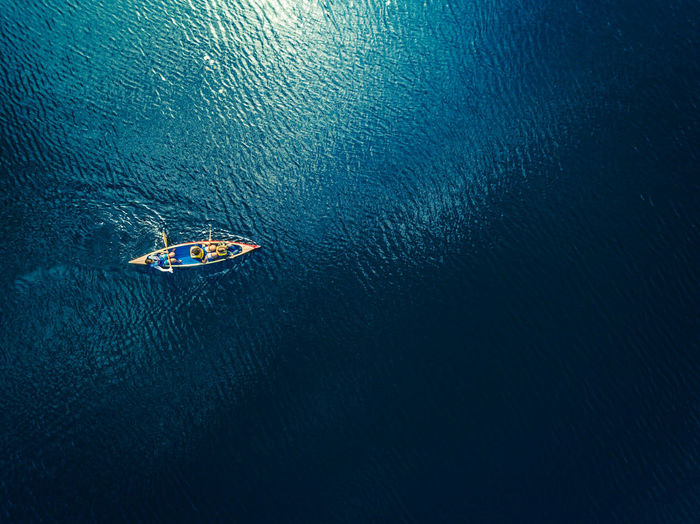 Directly Above View Of People Rowing Boat In Sea