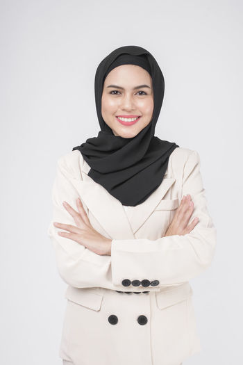 Portrait of a smiling young woman against white background