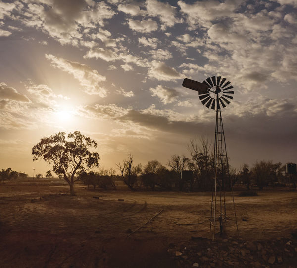 Windmill on field against sky at sunset