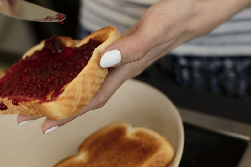 Cropped Hand Applying Jam On Bread