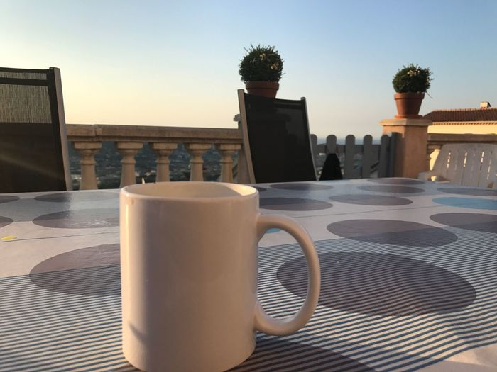 Close-up of coffee cup on table against clear sky