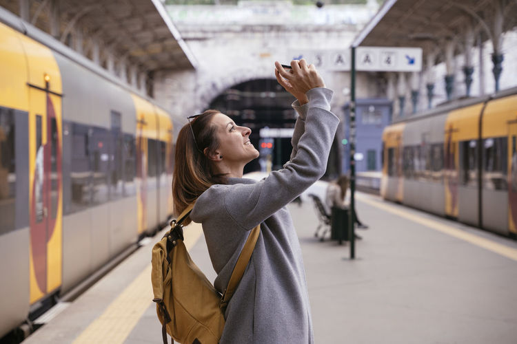 Rear view of woman standing by train at railroad station